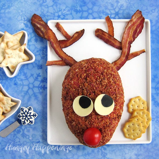 Rudolph cheese ball with bacon antlers on a white platter with bowls of star shaped and Christmas tree shaped crackers and a snowflake cheese knife all on a blue snowflake background.