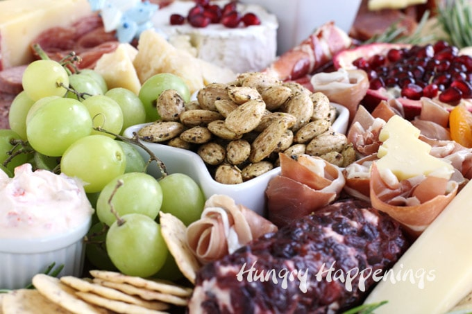 closeup picture of the items on the charcuterie board including Blue Diamond Nut-Thins, a cranberry coated goat cheese log, green grapes, Blue Diamond Gourmet Almonds, Parmigiano Reggiano Cheese, and more.
