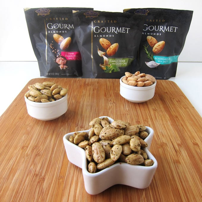 Bags of Blue Diamond Gourmet Almonds are set behind a cutting board that has small bowls of the nuts in them.