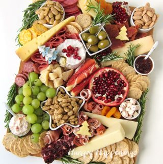Holiday charcuterie board filled with meat, cheese, fruits, herbs, gourmet almonds and almond crackers.