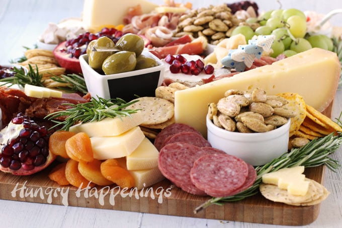 closeup image of a charcuterie board filled with cheese, salami, apricots, almonds, olives, crackers, rosemary, and more.