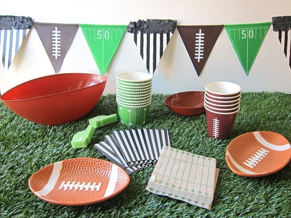 football themed party ware including plates, cups, bowls, napkins and boxes are sitting on astro turf with football themed pennants hanging on the wall behind