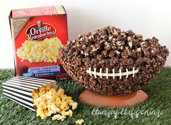 The football shaped chocolate popcorn bowl is set up on a football shaped bowl set on astro turf next to a box of Orville Redenbacher's Movie Theater Butter Popcorn and a black and white referee striped box with popcorn spilling out onto the astro turf.