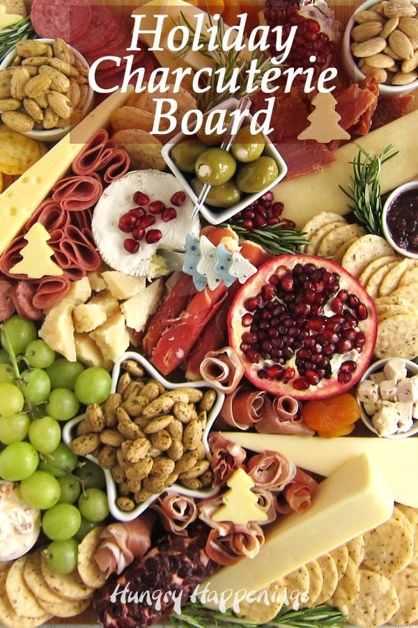 closeup image of all the charcuterie board topped with proscuitto, salami, summer sausage, goat cheese logs, Parmigiano Reggiano, Balsamic Cheese, soft cheeses and hard cheese, cheese spreads, and preserves along with Blue Diamond Gourmet Almonds, Nut Thins and some fresh fruit and rosemary.