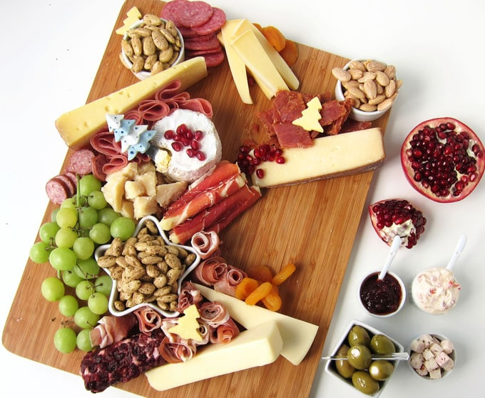 Add fruit, olives, and spreads to the meat, cheese, and nuts on the cutting board.