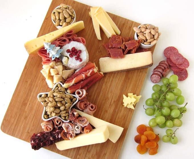 a cutting board topped with bowls of almonds, meats, and cheeses are set next to other items like grapes and dried apricots which will be added to the charcuterie board
