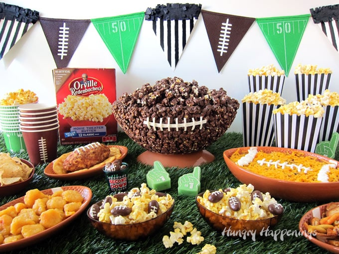 Super Bowl Party food displayed on a table covered with astro turf. Football shaped bowls filled with taco tip, popcorn, a football shaped cheese ball are set in front of a chocolate popcorn bowl football and boxes of Orville Redenbacher's Popcorn. Pennants are hung behind the food.