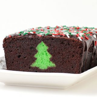 A chocolate thin mint Peek-a-Boo Christmas pound cake is cut open to reveal a green Christmas tree hiding inside.