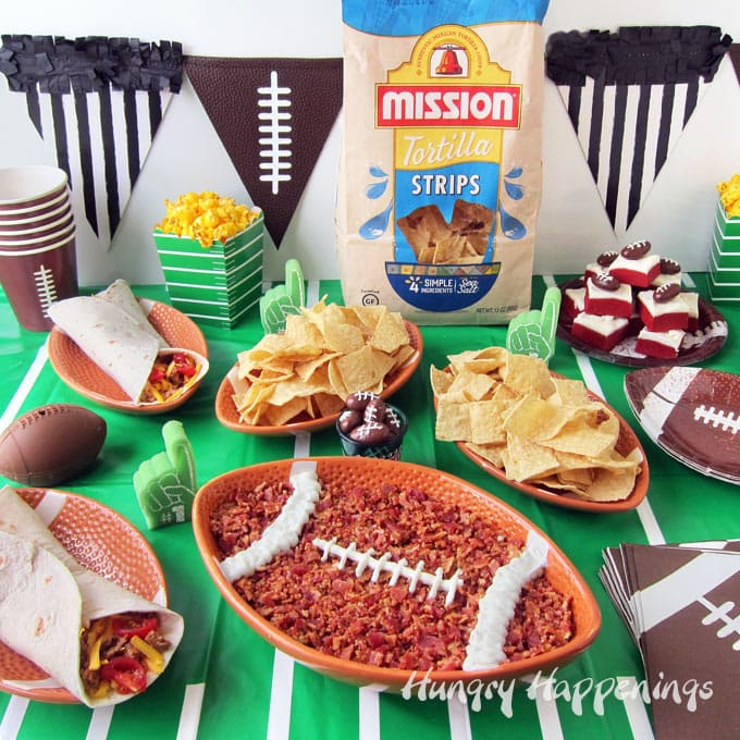 Artichoke Pesto Dip served in a football shaped ceramic bowl is set in the center of a table decorated with a football field table cloth and surrounded by more football shaped plates fill with Mission Tortilla Strips, soft tacos, football topped fudge, and popcorn.