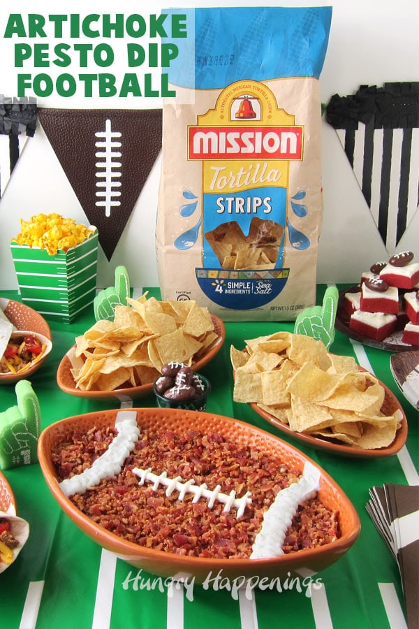 A football shaped bowl filled with Artichoke Pesto Dip topped with chopped bacon is decorated with sour cream and the dip is displayed with bowls of chips, popcorn, tacos, and football fudge.