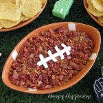 Bacon topped cheeseburger dip is served in a football shaped bowl.