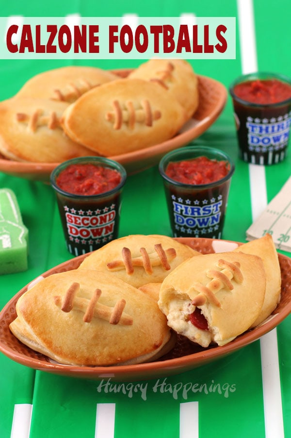 Football shapes calzones served on ceramic football plates are set next to football themed shot glasses filled with homemade marinara sauce on a table covered in a bright green football field table cloth.