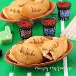 Football shapes plates topped with Calzone Footballs are set on top of a football field tablecloth along with shot glasses filled with homemade marinara sauce and tiny foam fingers and football field napkins.