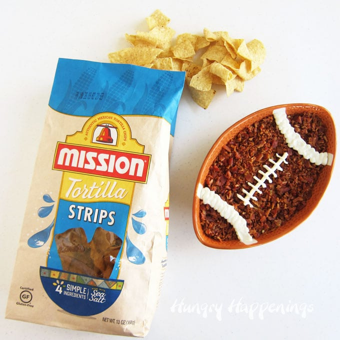 Mission Strips Tortilla Chips set next to the football shaped bowl filled with artichoke pesto dip that is decorated with bacon and sour cream to look like a football.