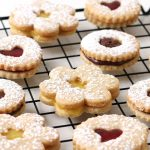 A variety of heart, daisy, and round shaped linzer cookies filled with raspberry preserves, lemon curd and Nutella are arranged on a cooling rack.
