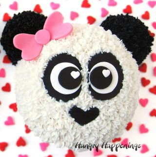 cute panda bear cake with a pink bow is decorated with frosting and modeling chocolate