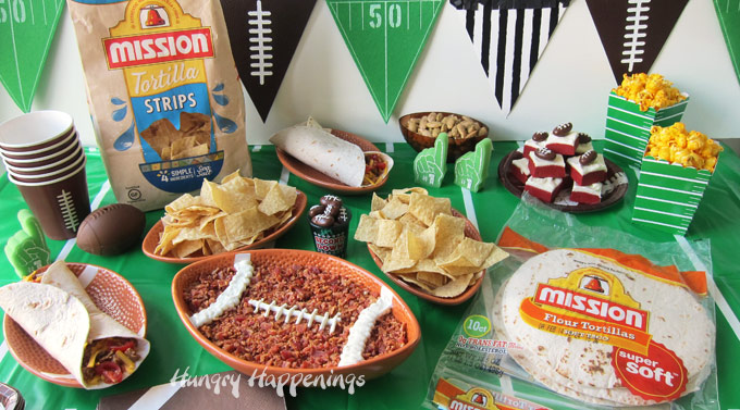 Big game party food on a table topped with a football field table cloth. Snacks are served in football shaped bowls and plates.