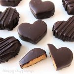 Chocolate Peanut Butter Hearts on a white background. The heart at the bottom of the picture is cut open revealing the peanut butter fudge inside a chocolate shell.