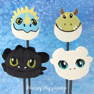 All four How To Train Your Dragon Lollipops including Night Fury (Toothless), Light Fury, Stormfly, and Meatlug, are set in front of a blue watercolor backdrop.