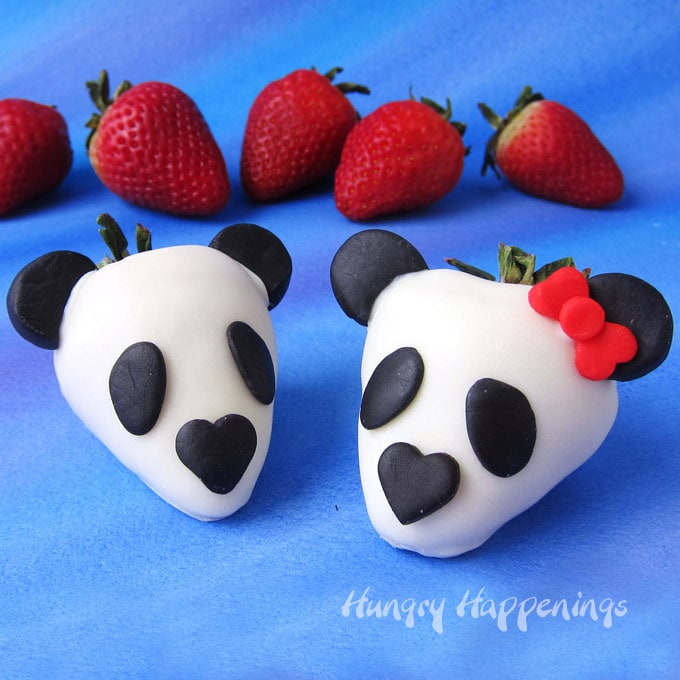two panda bear strawberries on a blue and purple watercolor background with strawberries set behind