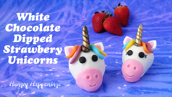 Two rainbow colored white chocolate dipped strawberry unicorns are sitting on a purple watercolor backdrop in front of 3 large strawberries.