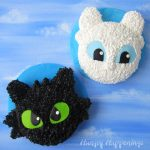 Toothless Cake and Light Fury Cake on a blue modeling chocolate covered round cake board are displayed on a blue sky watercolor background.