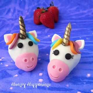 two white chocolate strawberry unicorns set on a purple and pink watercolor background with fresh strawberries set behind