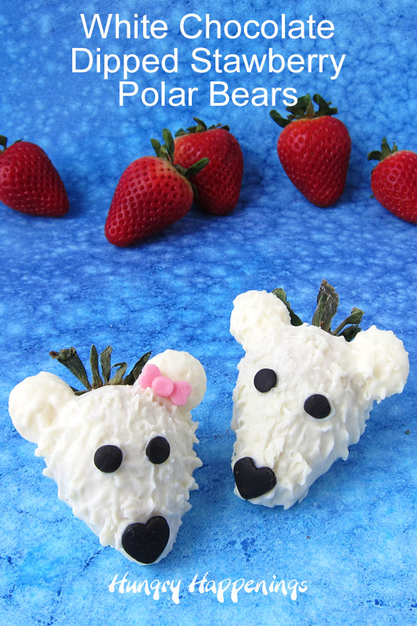 two white chocolate dipped strawberries are decorated with modeling chocolate to look like polar bears and are set on a blue watercolor background with strawberries in the background