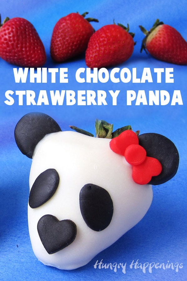 white chocolate dipped strawberry panda bear decorated with modeling chocolate placed in front of a grouping of strawberries