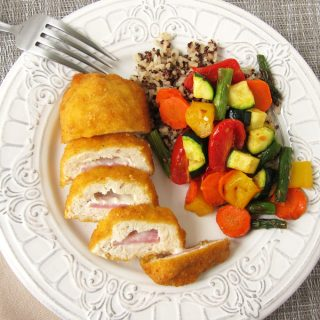 Barber Foods Cordon Bleu Stuffed Chicken Breasts cut open and served on a white plate alongside air fried vegetables and a blend of quinoa and rice.