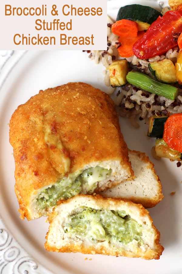 broccoli & cheese stuffed chicken breast on a white dinner plate served with roasted vegetables and rice and quinoa