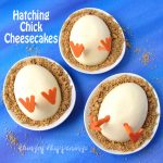 3 oval plates topped with hatching chick cheesecakes served on graham cracker crumbs on a blue watercolor background