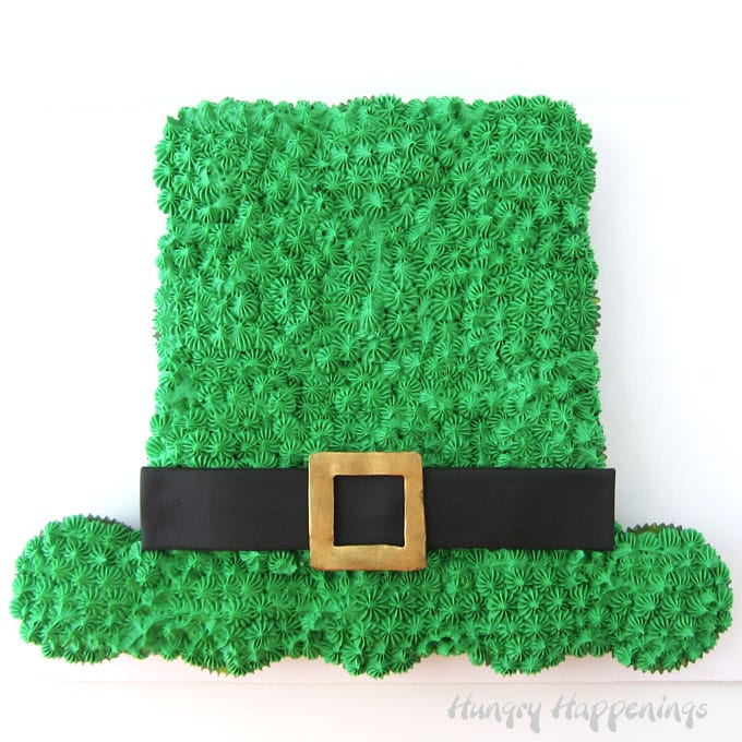Leprechaun Hat Cupcake Cake decorated with green frosting and a black modeling chocolate hat band with a gold modeling chocolate buckle.