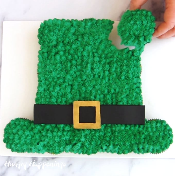 pull-apart leprechaun hat cupcake cake with someone pulling a cupcake from the cake