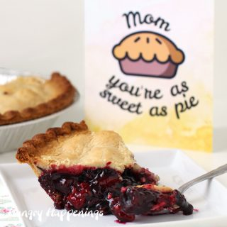 """a slice of Sara Lee Wildberry Pie with Zesty Lemon Crust sitting on a square white plate in front of the pie and a """"Mom, you're as sweet as pie"""" card"""
