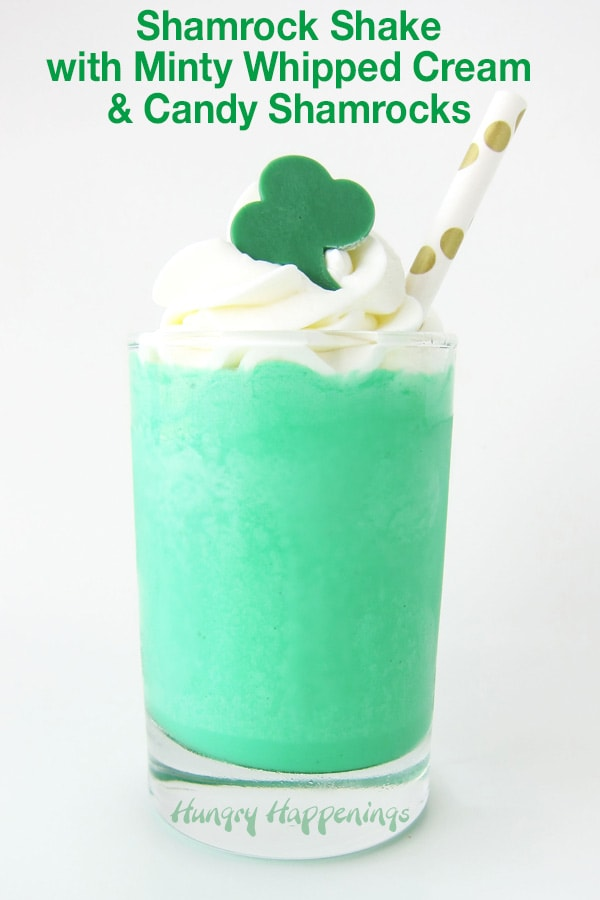 A bright green Shamrock Shake topped with a swirl of whipped cream and a green candy shamrock.
