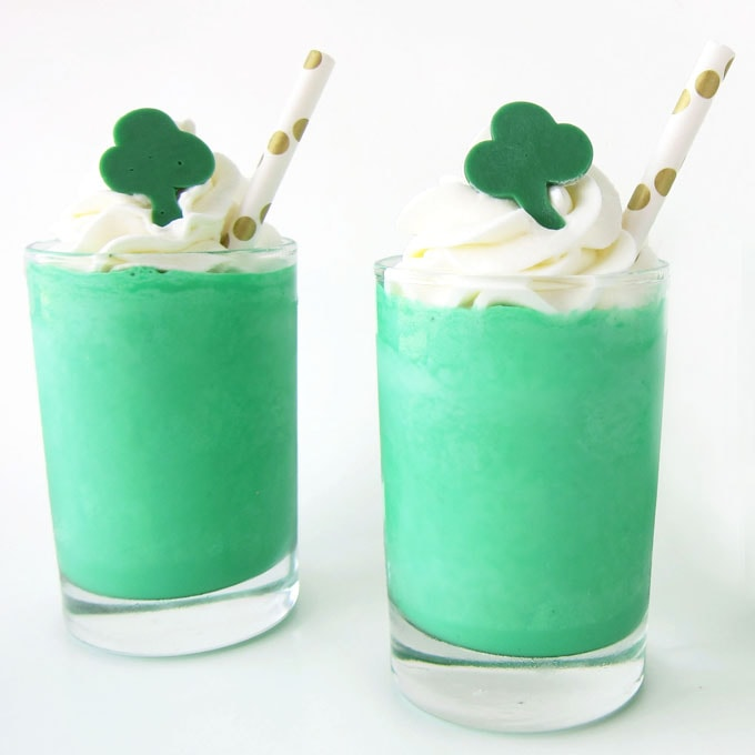 Shamrocks Shakes topped with a swirl of minty whipped cream and a green candy shamrock served with gold polka dot straws .