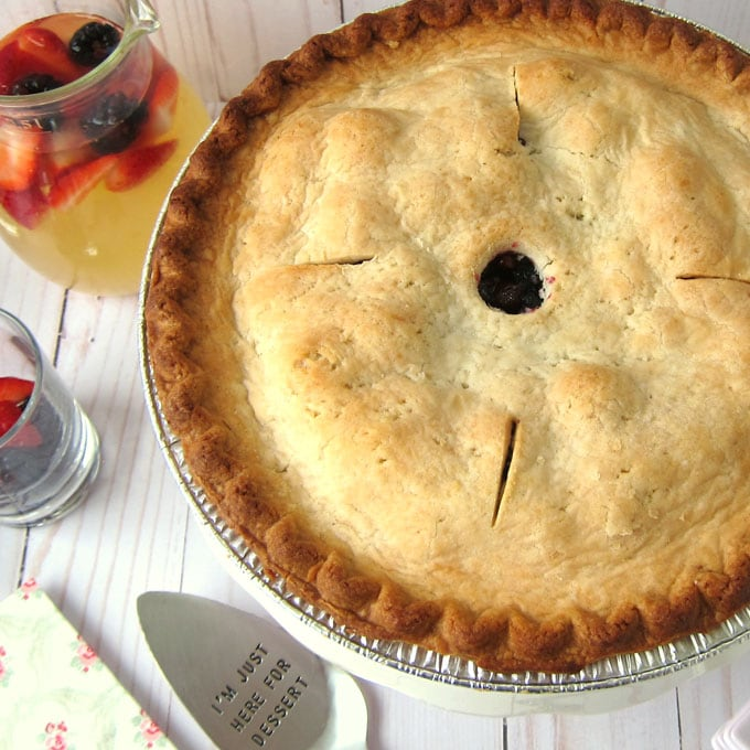whole wildberry pie set next to a pitcher of lemonade with fresh strawberries and blackberries