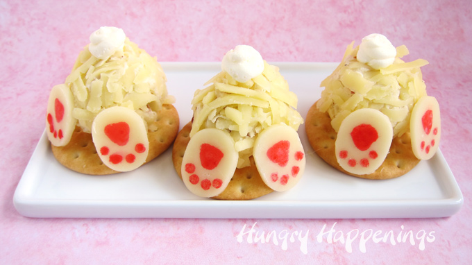 3 mini bunny butt cheese balls set on top of crackers on a white plate set on a pink background