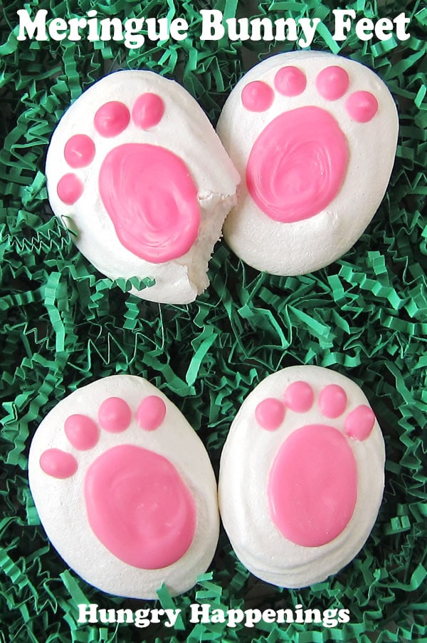 four meringue bunny feet set in pairs on green shredded paper Easter grass. One cookie has a bite taken out of it showing the inside of the crunchy meringue.