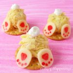 3 mini cheese ball bunnies with cream cheese tails and white cheddar cheese feet are set on round crackers displayed on a pink watercolor background
