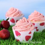 3 strawberry cupcakes wrapped in printable strawberry cupcake wrappers are set on grass in front of a blue sky background along with some fresh strawberries .