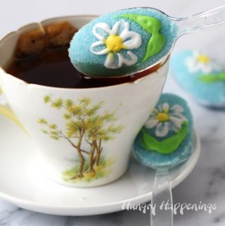 a sugar coated spoon is decorated with a royal icing and is being dipped in a cup of tea. There is another daisy sugar spoons sitting on the saucer and another on the marble table behind the cup.
