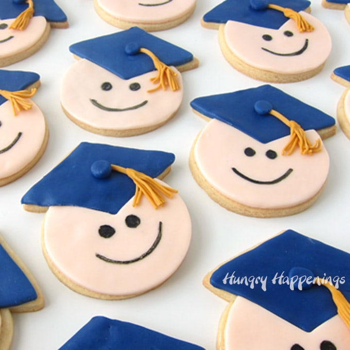cute graduation cookies decorated with modeling chocolate smiley faces and blue candy clay grad caps with gold tassels