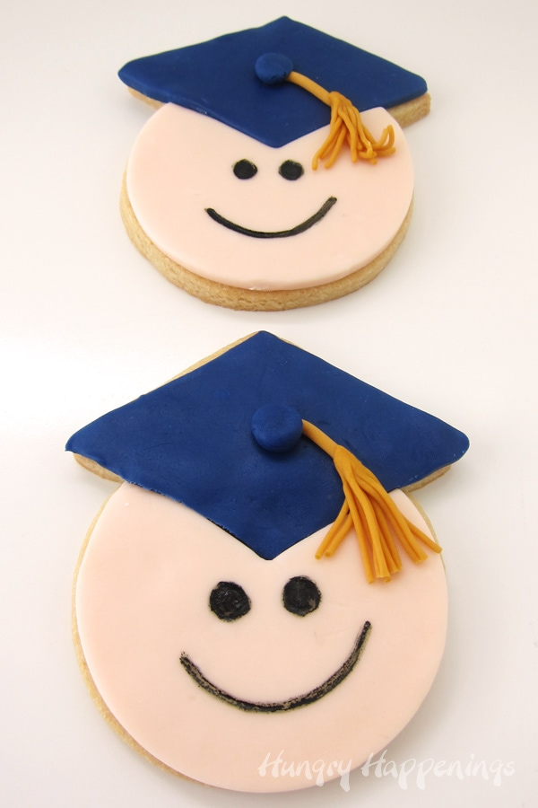 two graduate cookies wearing blue grad caps with gold tassels