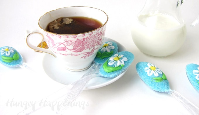 Daisy Sugar Spoons are set on and around a saucer with a cup of hot tea and a picture of cream