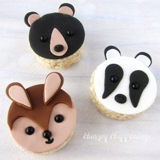 cute animal themed rice krispie treats including a black bear, a bunny, and a badger all decorated using fondant