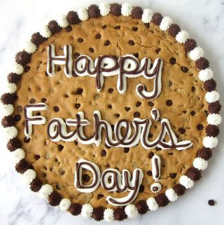 "giant chocolate chip cookie cake decorated with white marshmallow frosting and chocolate frosting with ""Happy Father's Day"""