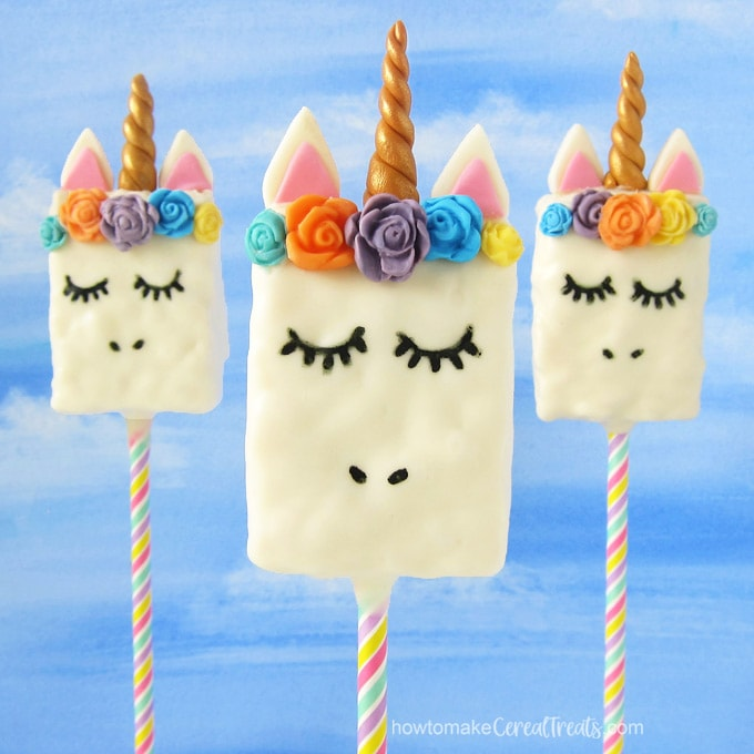 Three Unicorn Rice Krispie Treats on lollipop sticks are standing up in front of a blue sky backdrop