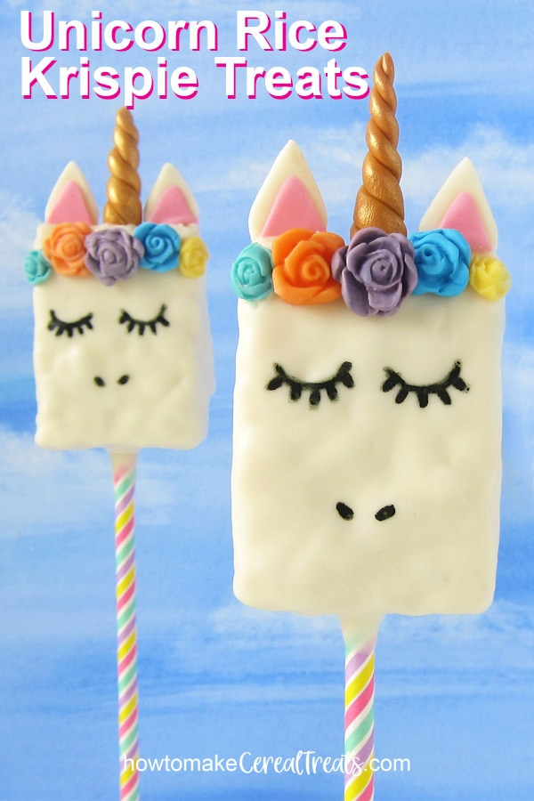 vertical image of two unicorn rice krispie treats on a blue watercolor background with test overlay